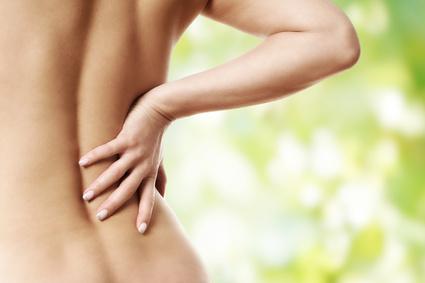 Frau mit Rückenschmerz vor bunten Hintergrund